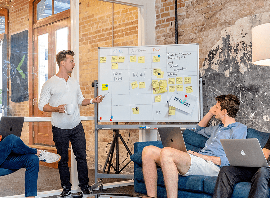 team leader next to a whiteboard talking to team members about a plan