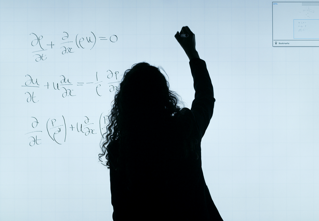 woman writing a mathematical equation onto a board